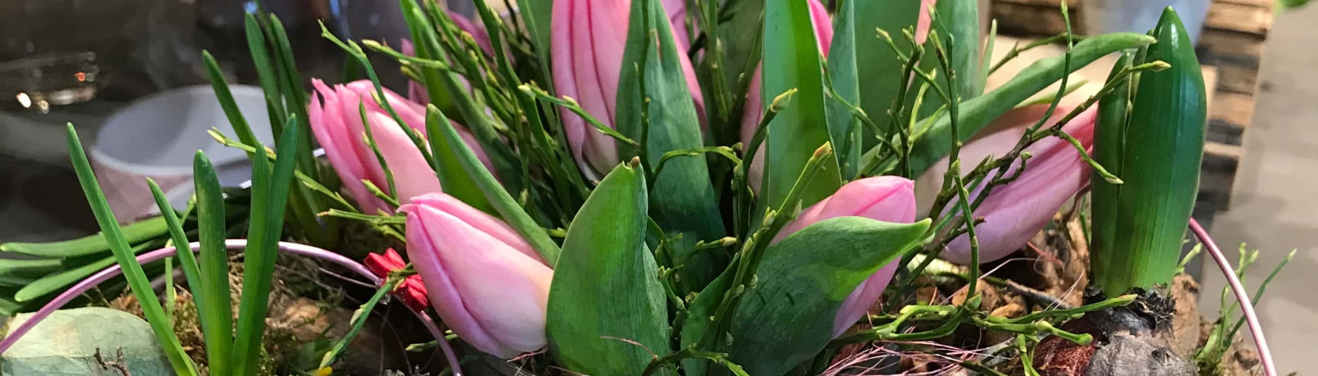 Ein frühlinghaftes Gesteck mit pinken Tulpen