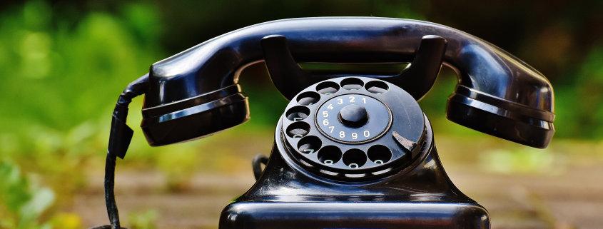 Ein schwarzes altes Telefon mit Wählscheibe steht draußen auf dem Boden