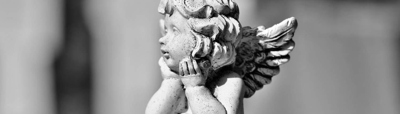 Eine sitzende Engelsfigur in schwarz-weiß