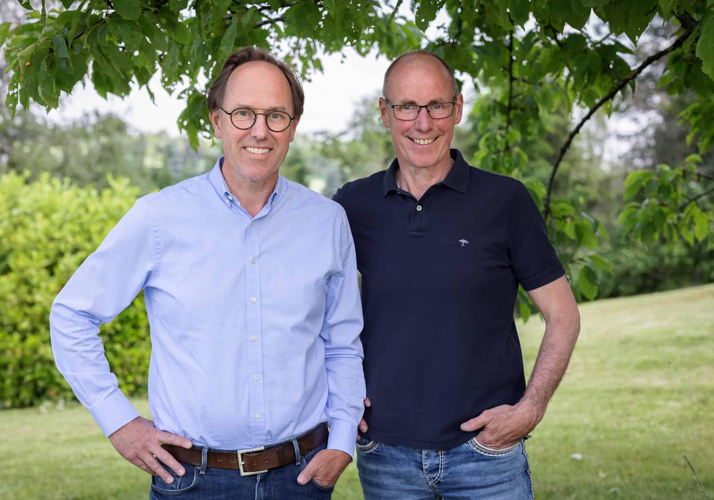 Zwei Männer stehen auf einer Wiese nebeneinander und lächeln in die Kamera