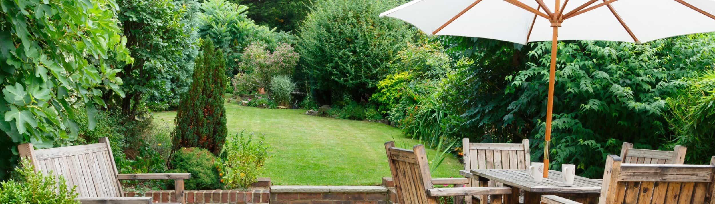 Eine Terasse mit Gartenmöbeln und Sonnenschirm und angrenzender Rasenfläche